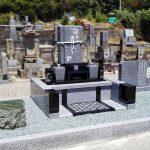 高松市の地域墓地でお墓の建替え工事。桜の彫刻をあしらった庵治石細目とインド黒の和洋折衷型デザイン墓石が完成しました。